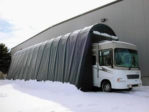RV inside covered garage in snow